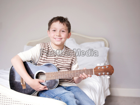 young boy sitting on bed playing