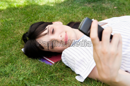 businesswoman laying in grass texting