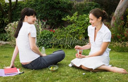 2 businesswomen eating lunch in park