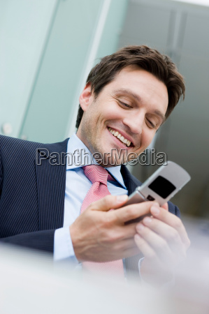 man smiling holding cell phone