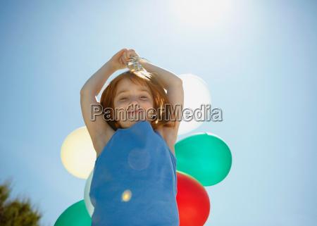 young girl holding balloons overhead