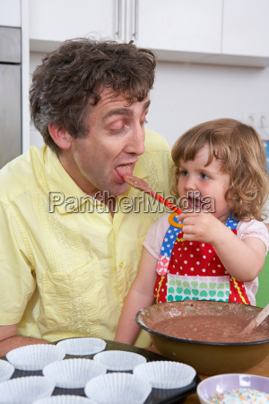 daughter is feeding father with batter