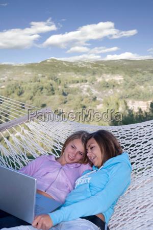 teen girls look laptop in hammock