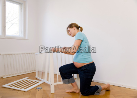 pregnant woman putting together baby bed