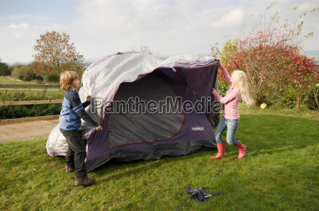 boy and girl putting up tent