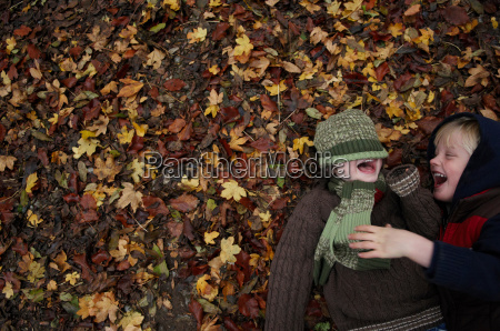 two friends lying on autumn leaves