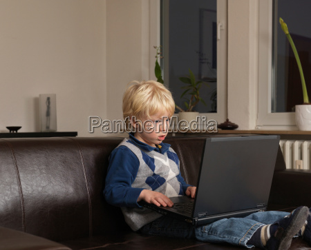 toddler working on laptop