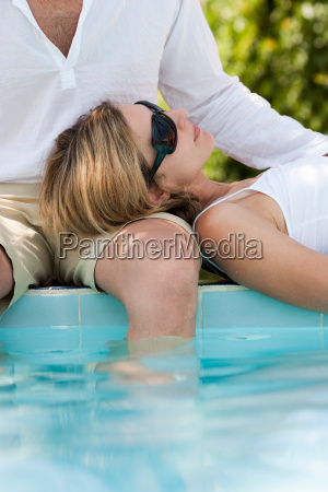 couple relaxing on pool