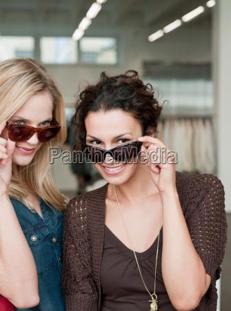 women shopping trying sunglasses