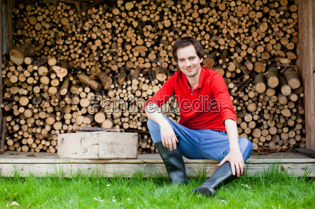 man sitting in front of haystack