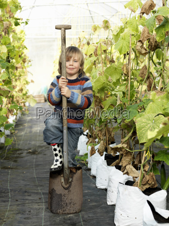 boy with shovel in green house
