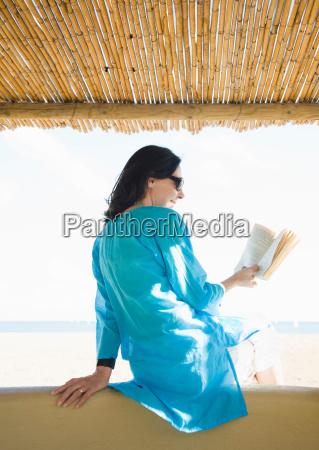 woman reading book on beach