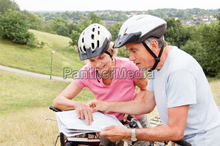 mature cyclists looking at map in