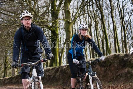 couple mountain biking in countryside