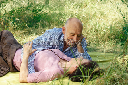 older couple embracing on picnic blanket