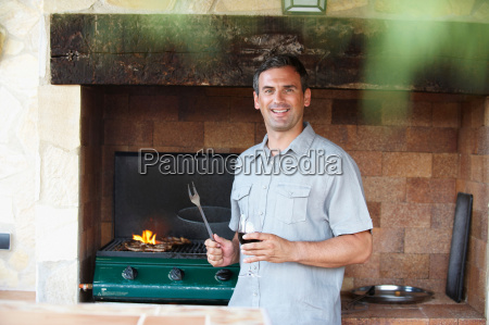 smiling man standing by barbeque