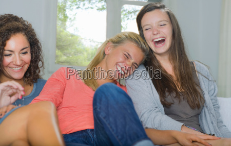 young women share a laugh sit