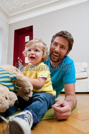 father and son playing on floor