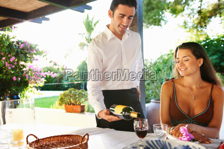 waiter pouring wine for woman at