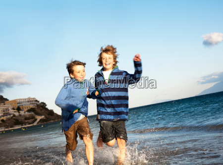 two boys running in surf on