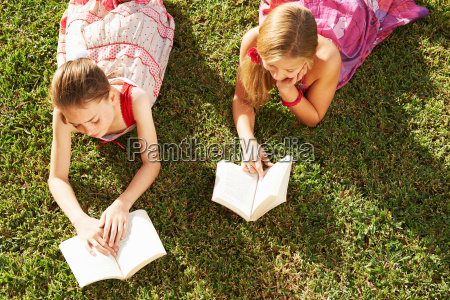 girls lying on grass reading books