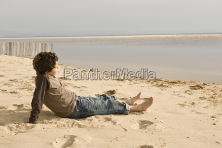 young boy sitting on sand looking