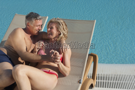 older couple laughing on sunbeds by