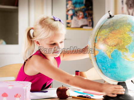 girl holding globe at desk