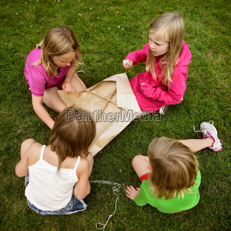 girls making a kite in grass