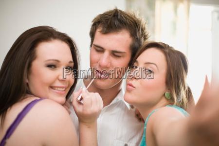 teenage girls putting makeup on boy