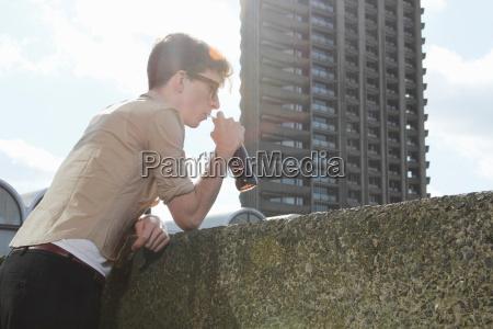 man drinking soda on balcony