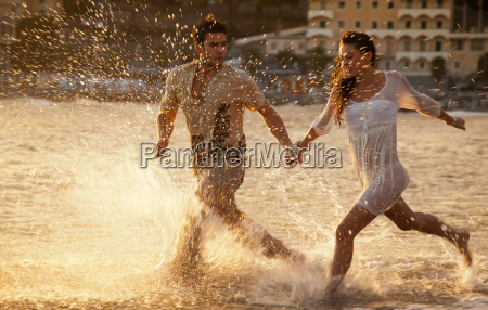 couple running in waves at beach