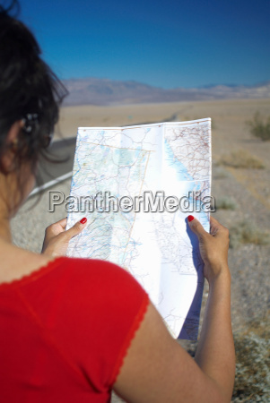 woman reading map on rural road