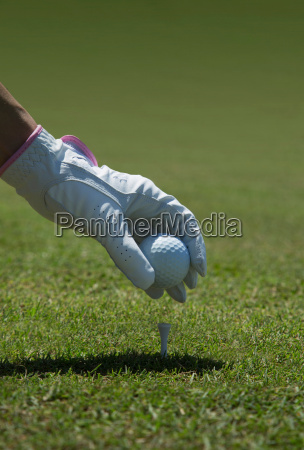 gloved hand placing golf ball on