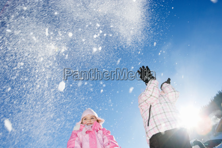 young girls throwing snow in the