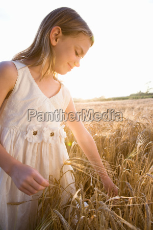young girl standing in corn field