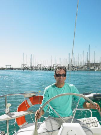 man wearing sunglasses steering yacht