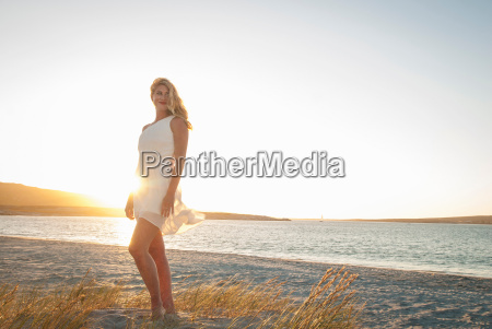 blond woman posing on beach at