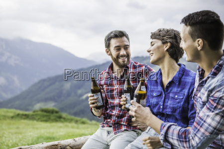 three young adult friends drinking beer