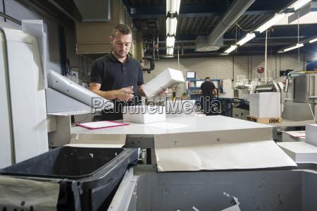 worker preparing paper for machine in