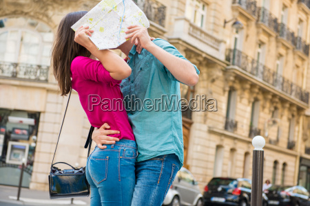 young couple hiding behind map paris