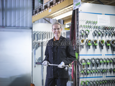 female worker in engineering factory holding
