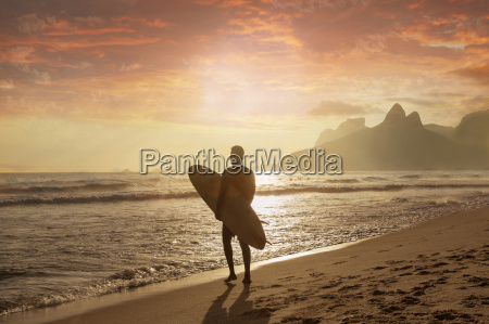 young man carrying surfboard on ipanema