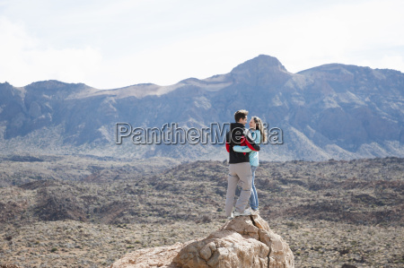mid adult couple standing on rock