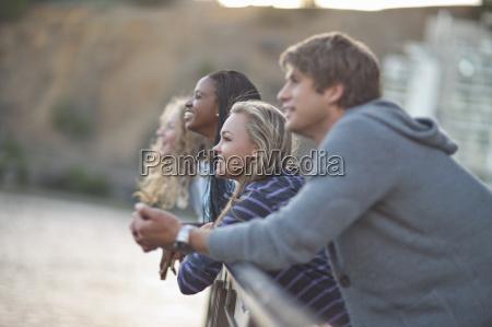 vier, junge, erwachsene, freunde, die, von, landhimmelsgeländer - 18240772