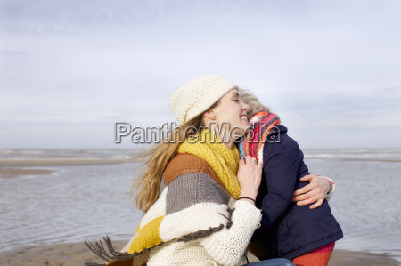 mid adult woman hugging daughter on