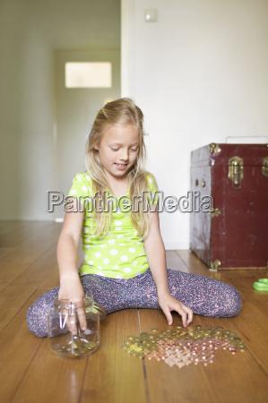 maedchen zaehlt muenzen aus sparglas