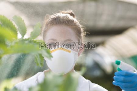 female scientist spraying liquid onto plant