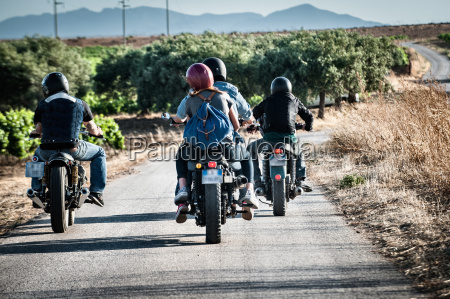 rear view of four friends motorcycling
