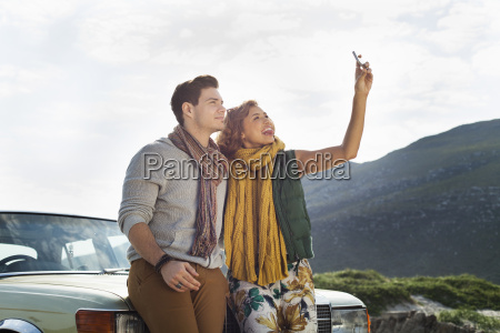 young couple leaning against car taking
